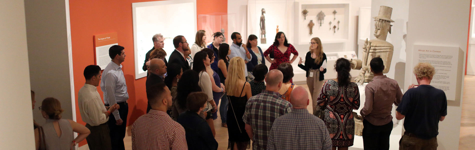 Visitors in a museum gallery listening to a talk led by an art educator