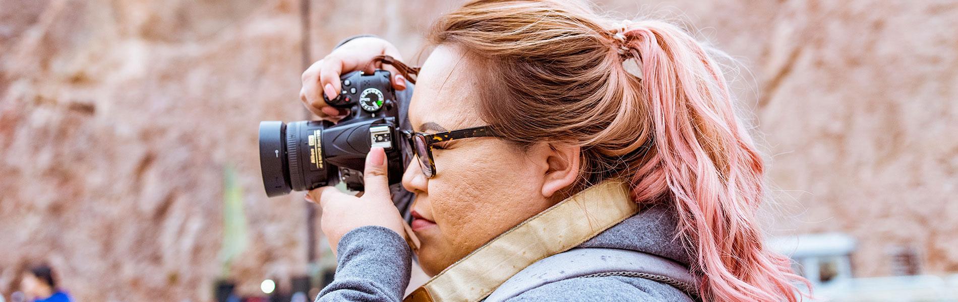 Woman aiming a dslr camera
