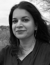 Manisha Sharma, brunette woman, long hair, smiling, wearing a necklacea